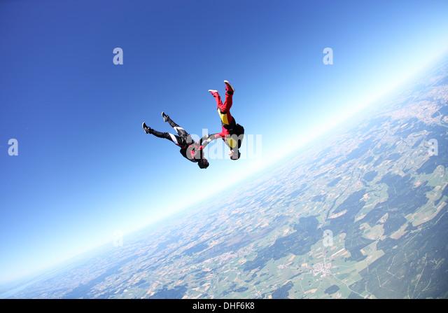 Weibliche Fallschirmspringer kopfüber über Leutkirch, Bayern, Deutschland Stockbild