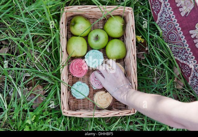 Hand unter Kuchen aus Korb mit Kuchen und Äpfel Stockbild