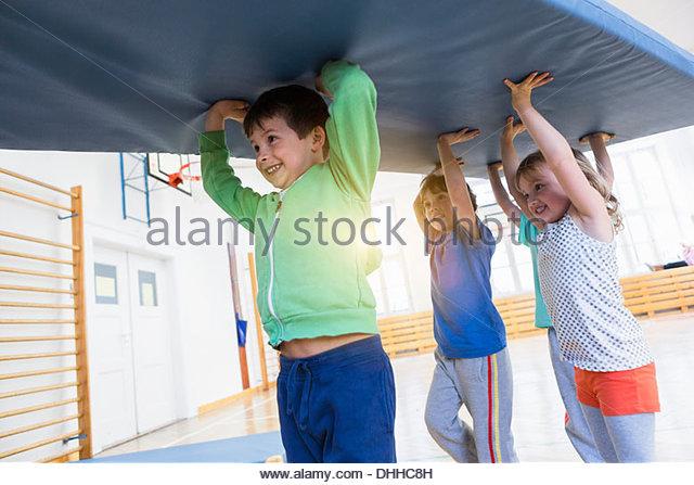 Jungen tragen blaue Gymnastikmatte über ihren Köpfen Stockbild