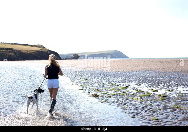 Frau zu Fuß Hund am Strand, Wales, UK Stockbild