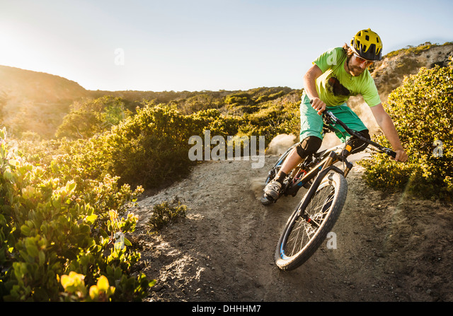 Junger Mann Mountainbiken auf Feldweg, Monterey, Kalifornien, USA Stockbild