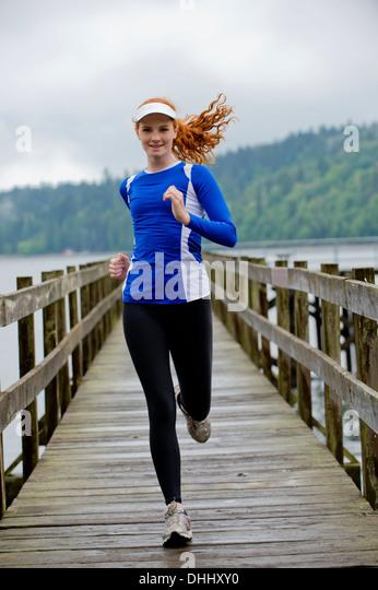 Teenager-Mädchen, die auf Pier, Bainbridge Island, Washington, USA Stockbild