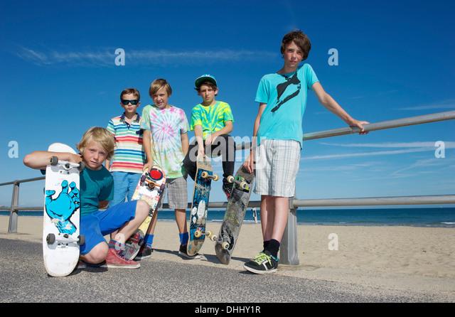 Porträt von fünf jungen mit Skateboards an Küste Stockbild
