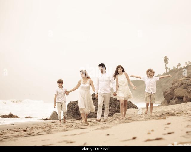Schöne junge Familie zu Fuß am Strand in Malibu, Kalifornien Stockbild
