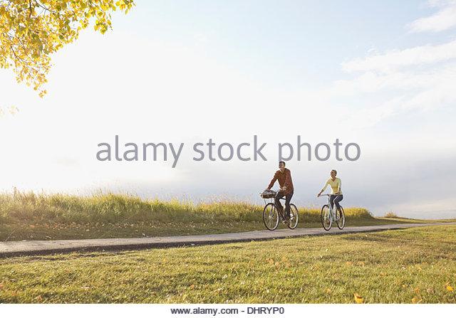 Voller Länge des Paares Radfahren auf Landstraße Stockbild