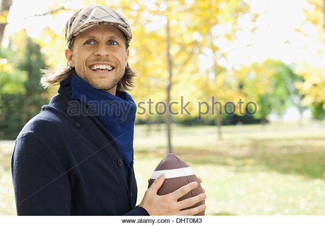 Glücklich Mitte erwachsenen Mannes spielen American Football im park Stockbild