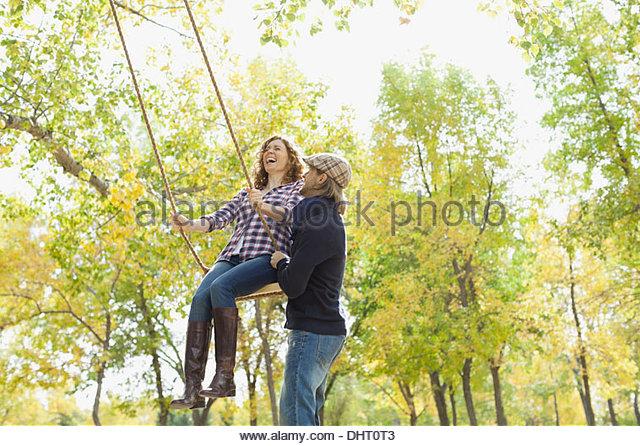 Mitte erwachsener Mann schob Frau auf Schaukel im Park im Herbst Stockbild