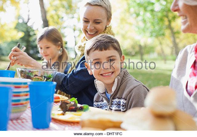Porträt von fröhlicher Junge mit Familie am Esstisch im park Stockbild