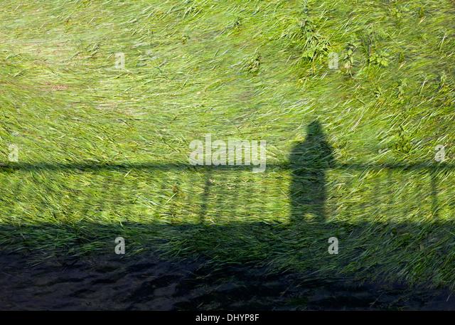 Schatten einer Person und einem Zaun Stockbild