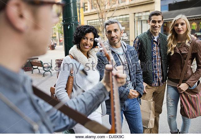 Fußgänger, die Straßenmusiker anhören Stockbild