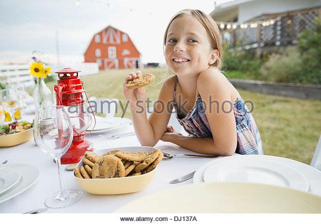 Mädchen hält Cookie am Esstisch im freien Stockbild