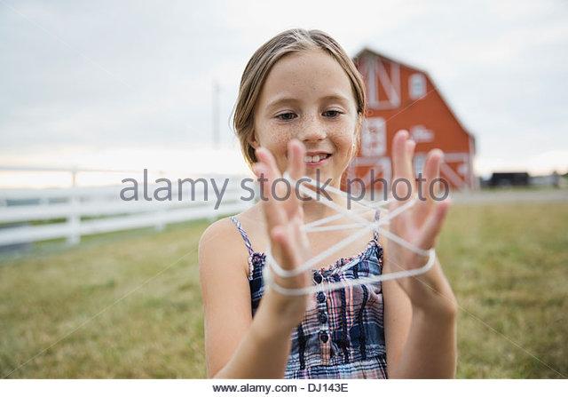 Junges Mädchen spielen Katzen Wiege auf Bauernhof Stockbild