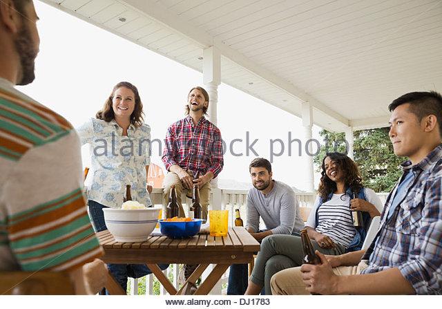 Multiethnische Freunde genießen Getränke auf Veranda Stockbild