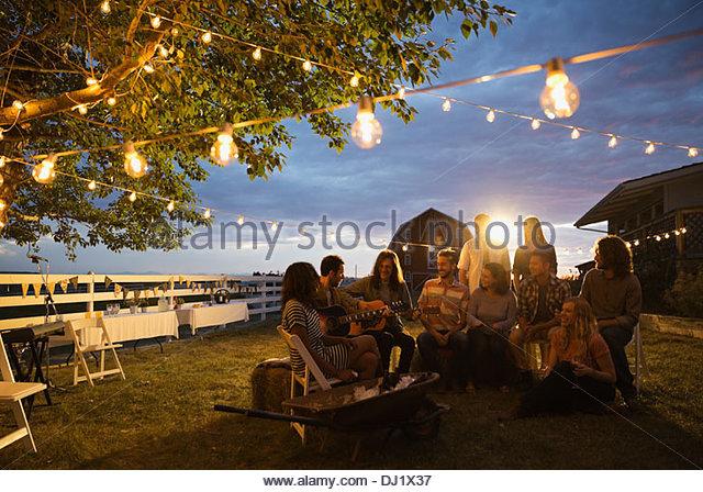 Gruppe von multiethnischen Freunden anhören Gitarristen während Party in der Abenddämmerung Stockbild
