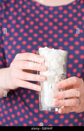 Frau hält ein Glas gefüllt mit Würfelzucker Stockbild