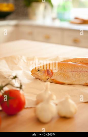 Nahaufnahme von ganzer Fisch, Knoblauch und Tomaten kochen Zutaten auf Küchentisch Stockbild