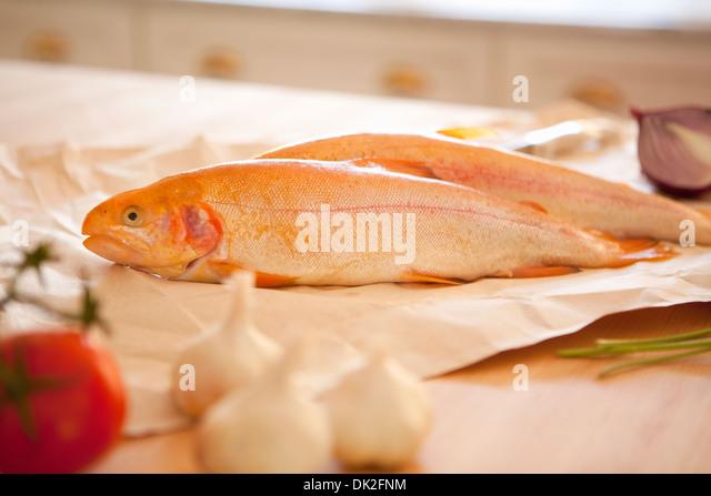 Nahaufnahme eines ganzen Fisch, Knoblauch und Tomaten Zutaten auf Küchentisch Stockbild