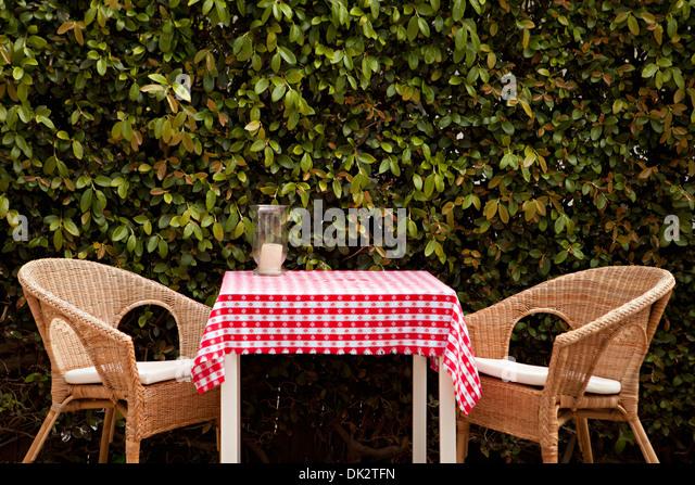 Korbsessel bei Terrassentisch mit roten und weißen Tischdecke Stockbild