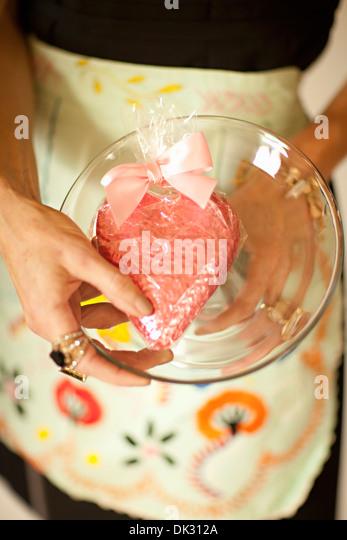 Erhöhte Ansicht schließen eingewickelt Mittelteil Frau in Schürze Holding Herzform Valentinstag Cookie Stockbild