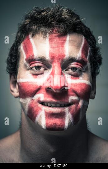 Porträt von lächelnden Mann mit britischer Flagge gemalt auf seinem Gesicht. Stockbild