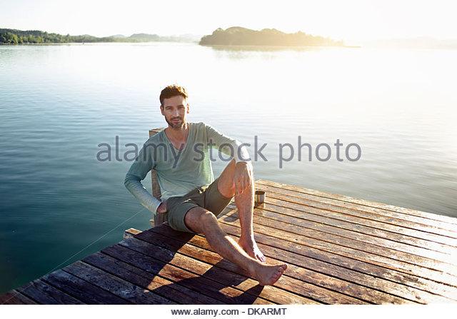 Porträt von reifer Mann sitzen auf decking See, München, Deutschland Stockbild