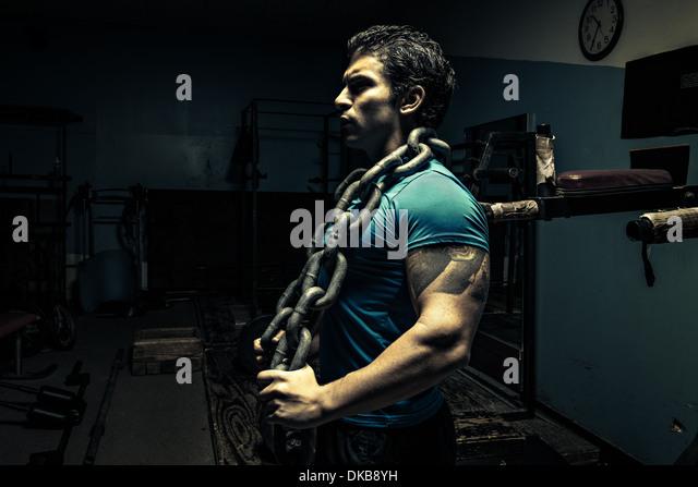 Gewichtheber in dunklen Turnhalle, Kette um den Hals Stockbild