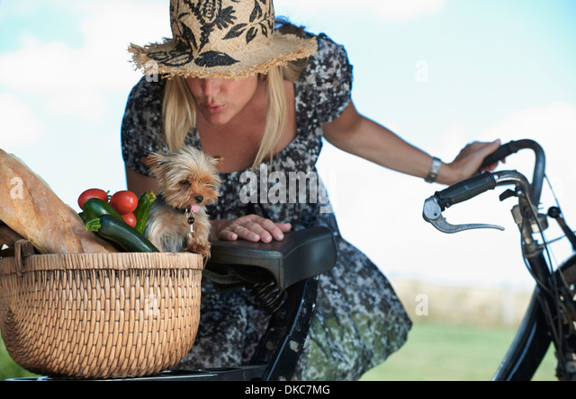 Reife Frau auf e-Bike mit Hund und Gemüse im Korb Stockbild