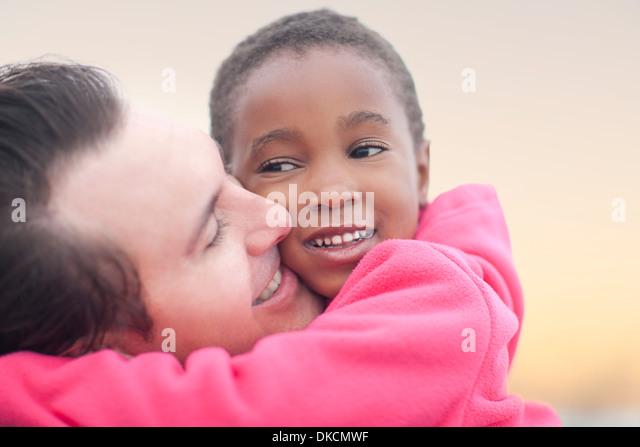 Mann umarmt Kind Stockbild