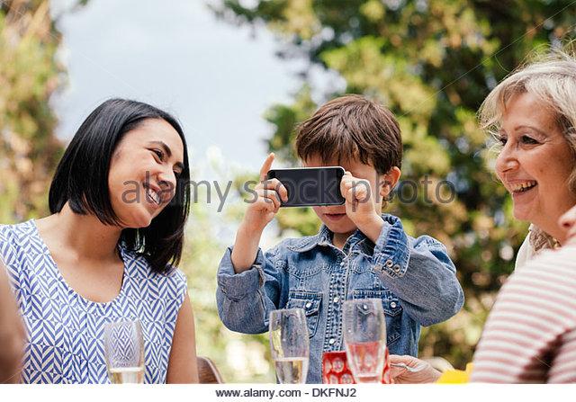 Junge, die Aufnahme eines Bildes mit Telefon am Familienfest Stockbild