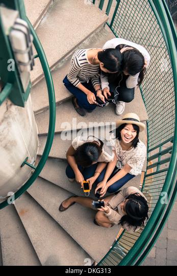 Fünf junge Frauen sitzen auf Stufen Blick auf smartphones Stockbild