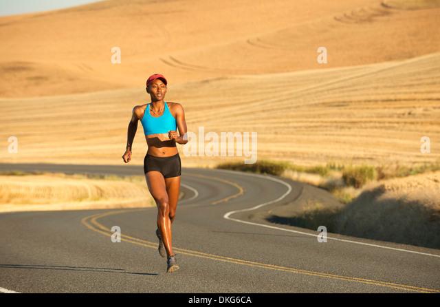 Junge Frau, die auf Straße, Bainbridge Island, Washington State, USA Stockbild
