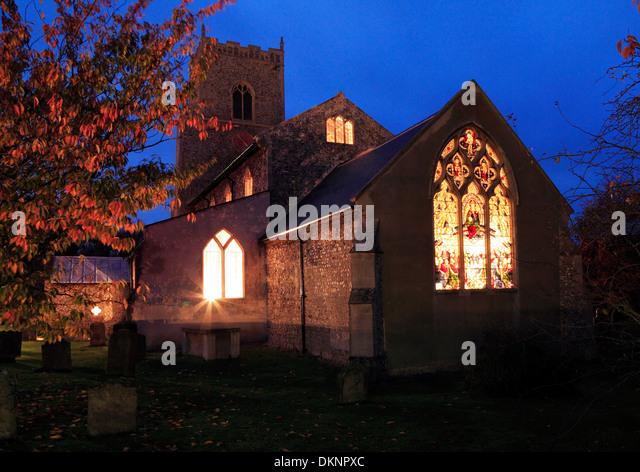 Brancaster Kirche, Ost-Fenster Lichter leuchten durch Glasfenster in der Nacht, Norfolk, England UK Stockbild