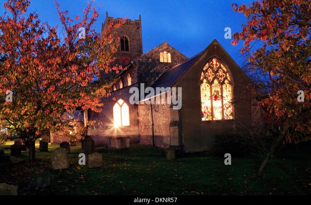 Brancaster Kirche, Lichter leuchten durch Glasfenster in der Nacht, Norfolk, England UK Stockbild