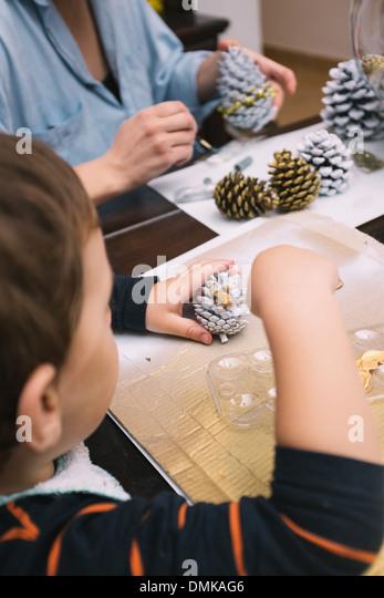 Kleiner Junge und seine Mutter sind Tannenzapfen zu Weihnachten malen. Stockbild