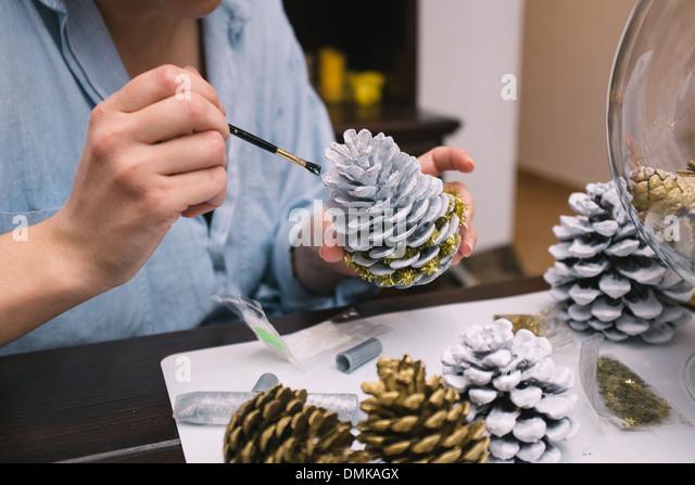 Frau malt Tannenzapfen bei ihr zu Hause Stockbild