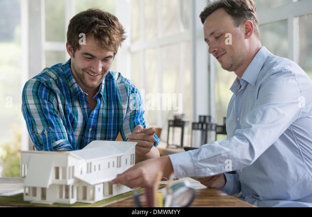 Zwei Männer ein Architekturmodell eines Hauses zu betrachten. Stockbild