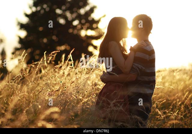 Junges Paar in Liebe im Kornfeld, küssen bei Gegenlicht Stockbild