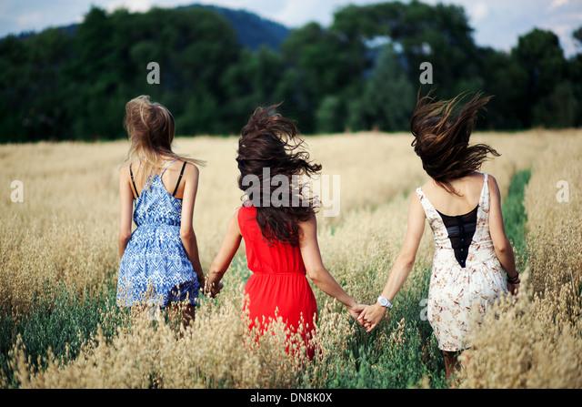 Drei Frauen gehen hand in hand durch ein Kornfeld Stockbild