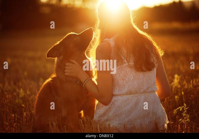 Frau mit Hund sitzt auf einer Wiese bei Sonnenuntergang Stockbild