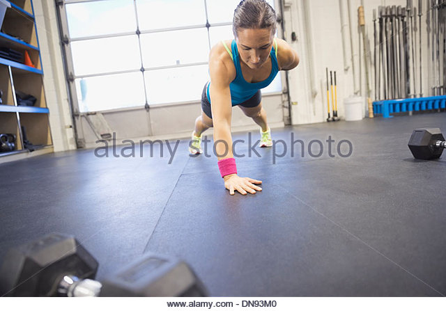 Entschlossenen Frau tun einem Arm Liegestütze in Turnhalle Stockbild
