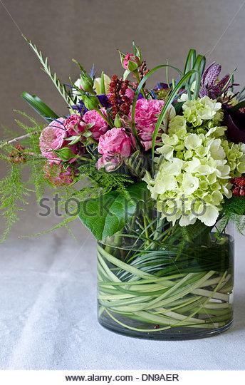 Frühling Blumen-Arrangement mit rosa, lila und weißen Blüten in klarem Glasvase auf helle Tischdecke. Stockbild