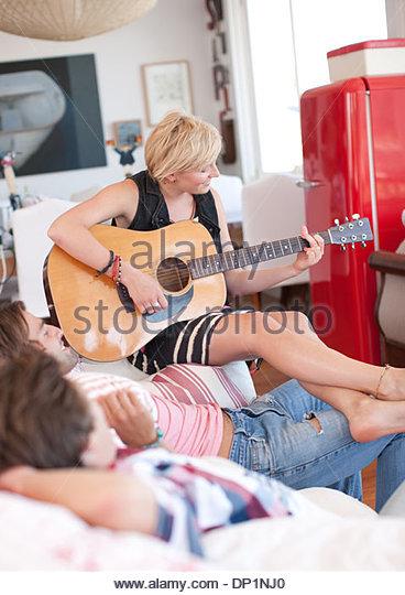 Frau mit nackten Füßen Gitarre für Männer auf sofa Stockbild