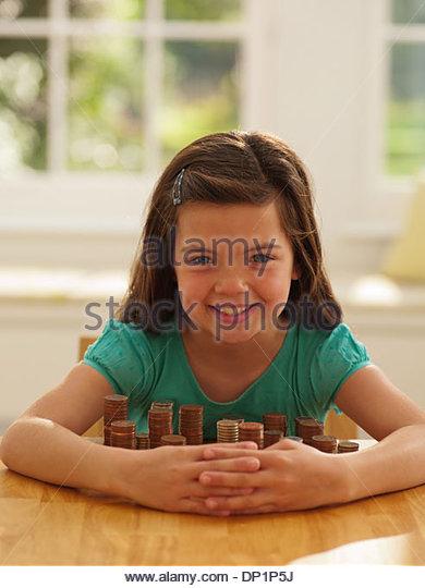 Lächelndes Mädchen Schutz Stapel von Münzen Stockbild