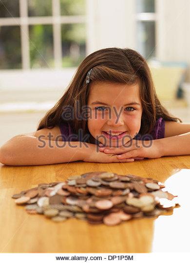Lächelndes Mädchen Blick auf Haufen von Münzen Stockbild