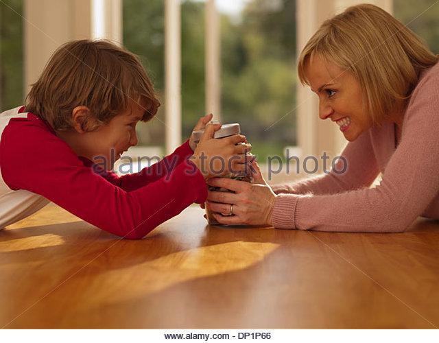 Mutter und Sohn halten am Glas voller Münzen Stockbild
