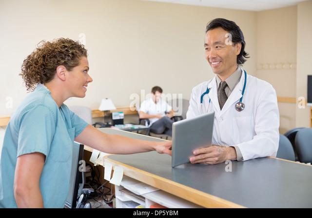 Arzt und Krankenschwester Krankenhaus Empfang Digital-Tablette mit Stockbild