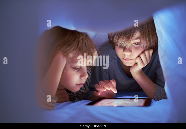 Brüder unter der Bettdecke mit digital-Tablette Stockbild