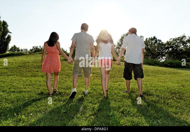 Gruppe junger Erwachsener zu Fuß und Hand in Hand Stockbild
