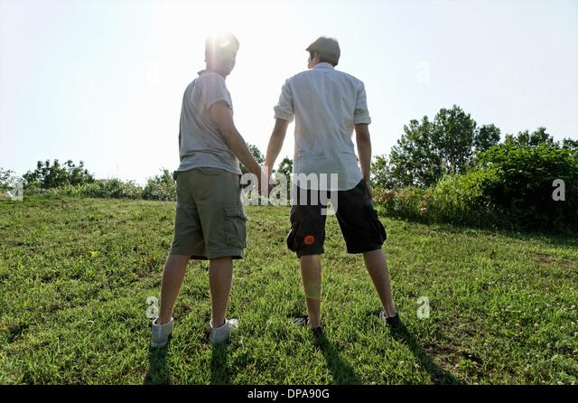 Zwei junge Männer zu Fuß und Hand in Hand Stockbild