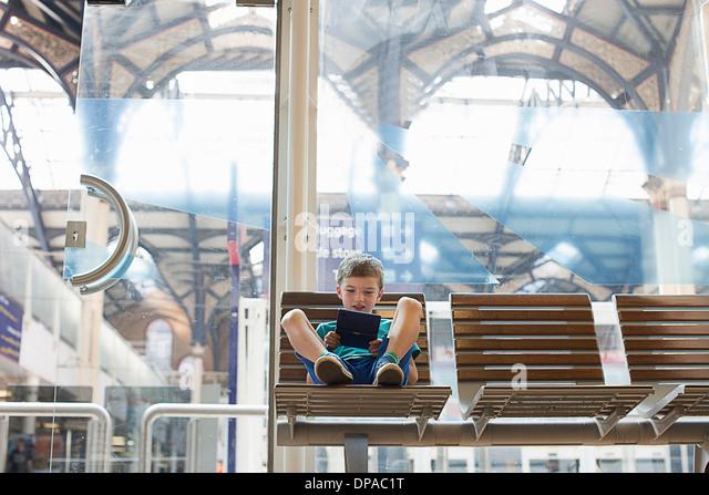 Kleiner Junge im Zug Bahnhof Wartezimmer Handheld-Spiel Stockbild